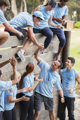 Teammates helping each other over wall on boot camp obstacle course - CAIF11937