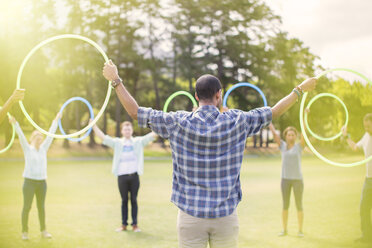 Team connected in circle with plastic hoops - CAIF11940
