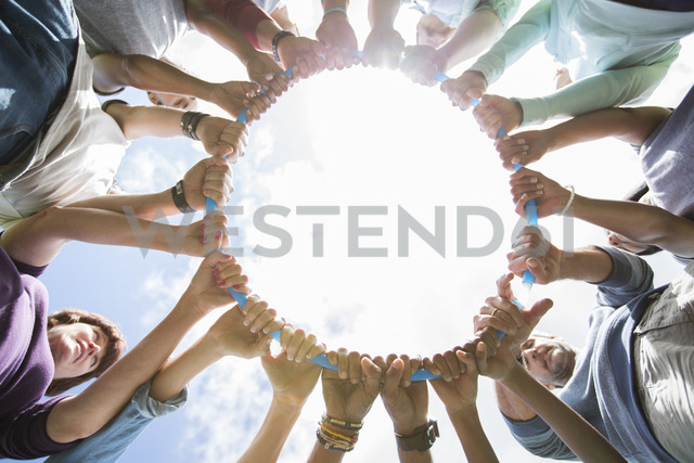 Team forming connected circle surrounding plastic hoop - CAIF11943
