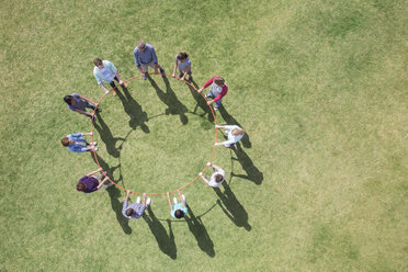 Overhead view of team connected in circle around plastic hoop - CAIF11946