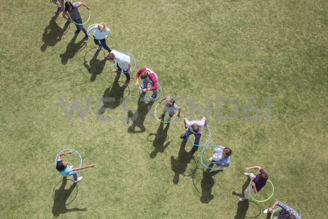 People spinning in plastic hoops in sunny field - CAIF11967 - Martin Barraud/Westend61
