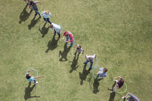 People spinning in plastic hoops in sunny field - CAIF11967