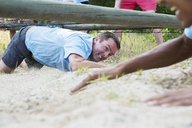 Determined man crawling under net on boot camp obstacle course - CAIF11970