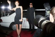 Paparazzi photographing smiling celebrity arriving at event - CAIF12006