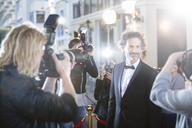 Smiling celebrity in tuxedo being photographed by paparazzi at red carpet event - CAIF12009