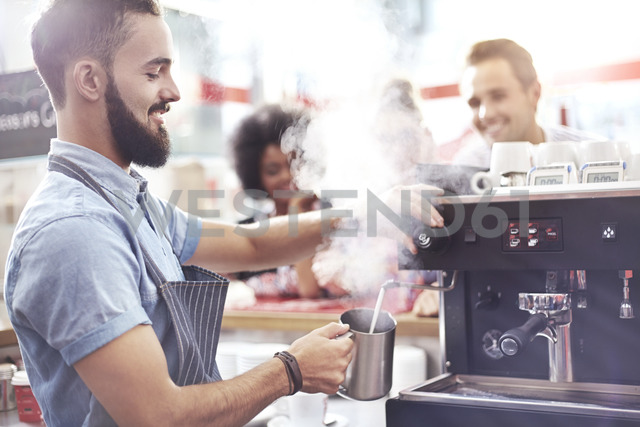 Barista steaming milk in cafe - CAIF12039