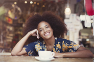 Portrait smiling woman with afro drinking coffee in cafe - CAIF12090