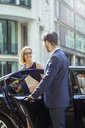 Chauffeur opening car door for businesswoman - CAIF12105