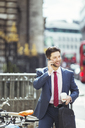 Businessman talking on cell phone on city sidewalk - CAIF12108