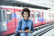 Smiling woman standing in train station - CAIF12123