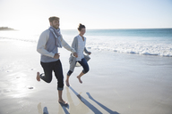 Young couple holding hands and running on beach - CAIF12132