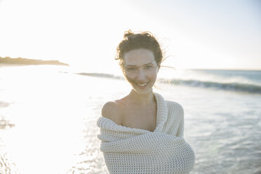 Portrait of young woman wrapped in blanket on beach - CAIF12135