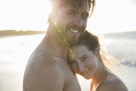 Portrait of young couple embracing on beach - CAIF12138