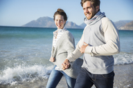 Young couple holding hands and walking on beach - CAIF12141