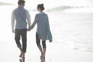 Young couple holding hands and walking on beach - CAIF12153