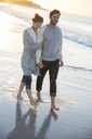 Young couple walking on beach in evening sun - CAIF12159