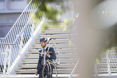 Businessman in suit and helmet carrying bicycle down urban stairs - CAIF12168