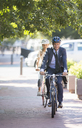 Businessman in suit and helmet riding bicycle on path - CAIF12171
