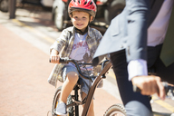 Portrait smiling boy riding bicycle on sunny road - CAIF12174