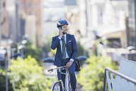 Businessman in suit and helmet sitting on bicycle talking on cell phone in city - CAIF12177