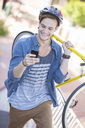 Young man with helmet carrying bicycle and texting on cell phone - CAIF12180
