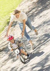 Mother pushing son with helmet on bicycle in sunny park - CAIF12189