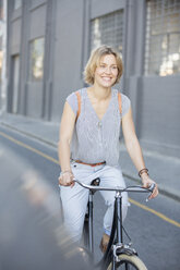 Smiling blonde woman riding bicycle on urban street - CAIF12192