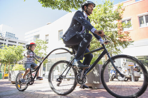 Businessman father in suit riding tandem bicycle with son on urban sidewalk - CAIF12195
