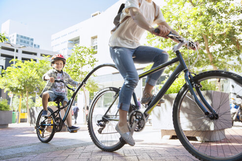 Son in helmet riding tandem bicycle with mother in urban park - CAIF12198