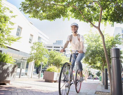 Smiling young woman with helmet riding bicycle in urban park - CAIF12204