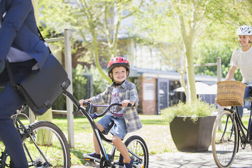 Portrait smiling boy in helmet riding tandem bicycle with father in park - CAIF12210