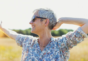 Enthusiastic senior woman with arms outstretched in sunny field - CAIF12216
