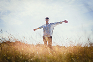 Carefree senior woman running with arms outstretched in sunny field - CAIF12219