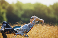 Carefree senior woman relaxing with book in sunny field - CAIF12222