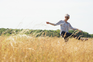 Playful senior woman dancing in sunny rural field - CAIF12228