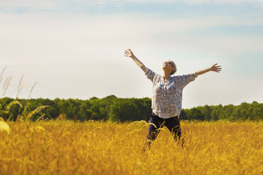 Exuberant senior woman with arms outstretched in sunny rural field - CAIF12231