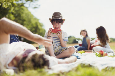 Smiling boy eating watermelon on blanket in sunny field - CAIF12267