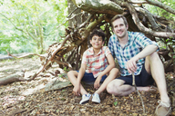 Portrait smiling father and son in woods - CAIF12285