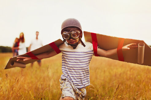 Boy with wings in aviator's cap and flying goggles in field - CAIF12288