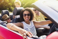 Portrait enthusiastic woman driving convertible with family - CAIF12303