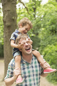 Playful son covering father's eyes in woods - CAIF12321