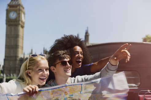 Enthusiastic friends with map below Big Ben clocktower in London - CAIF12324