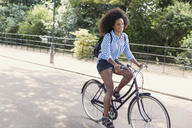 Woman with afro riding bicycle in park - CAIF12330