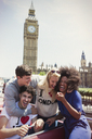 Enthusiastic friends riding double-decker bus below Big Ben clocktower, London, United Kingdom - CAIF12336