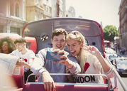 Couple taking selfie on double-decker bus, London, United Kingdom - CAIF12339