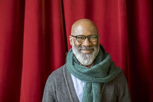 Portrait of smiling man wearing glasses and scarf in front of red curtain - FMKF04910