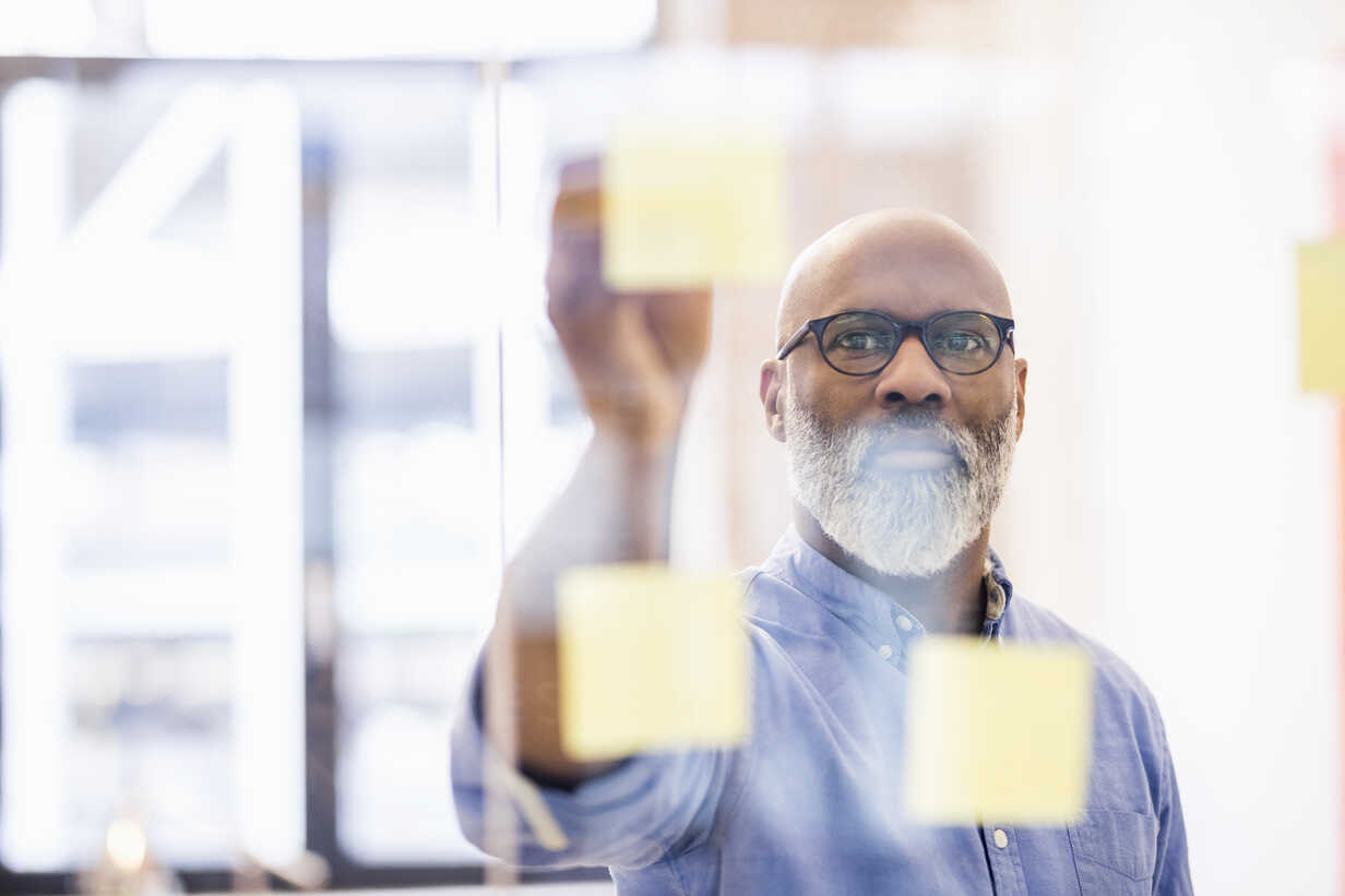 Portrait of businessman taking adhesive note from glass wall in office - FMKF04931 - Jo Kirchherr/Westend61