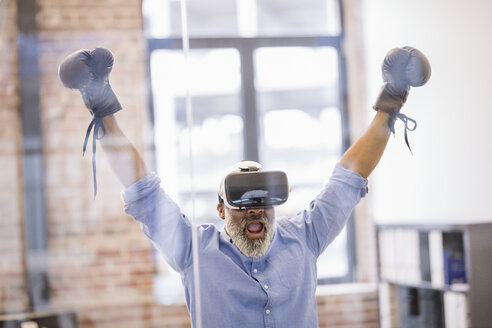 Portrait of businessman with Virtual Reality Glasses and boxing gloves in the office - FMKF04937