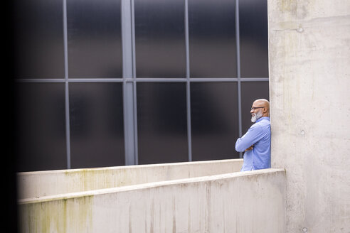 Pensive businessman leaning against concrete wall - FMKF04940