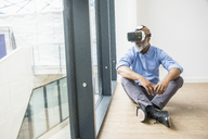 Businessman wearing VR glasses sitting on the floor at the window - FMKF04964